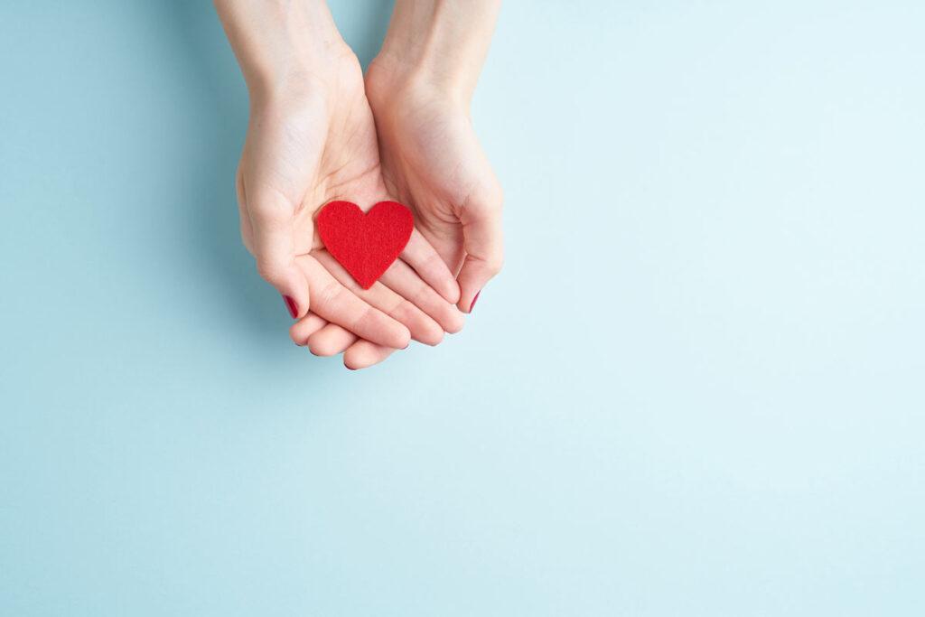 Hands holding a small felt heart cutout