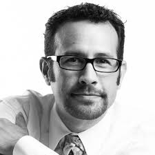 Smiling professional man with glasses, mustache and beard in a shirt and tie